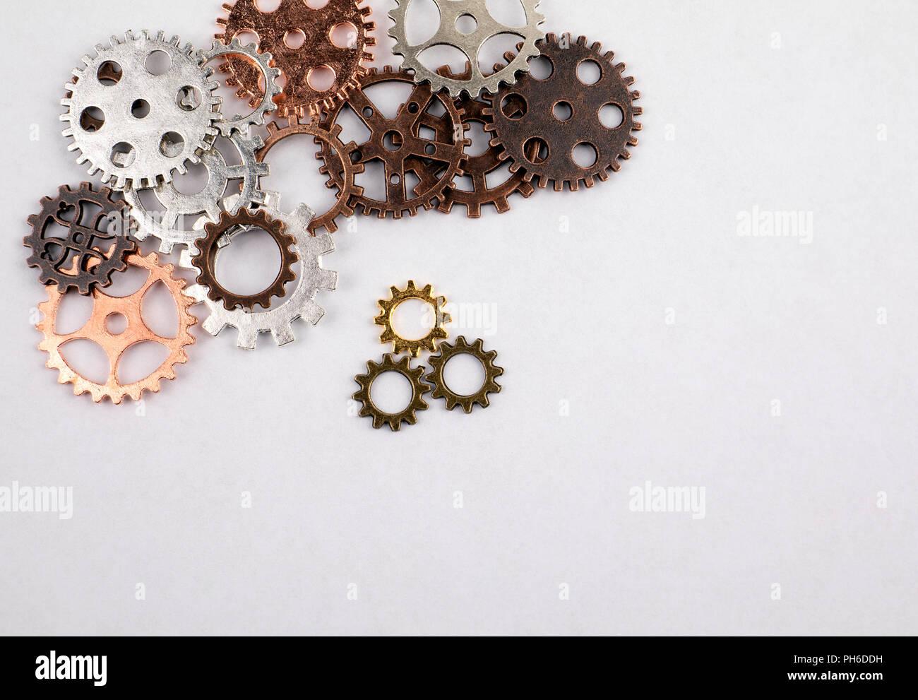Engranajes de diferentes tamaños y colores sobre un fondo blanco. Imagen De Stock