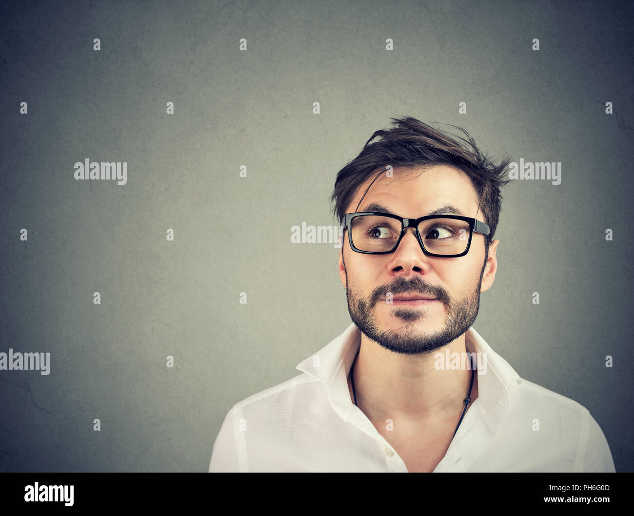Apuesto hombre barbado mirando hacia arriba en la contemplación la toma de decisión sobre fondo gris Imagen De Stock