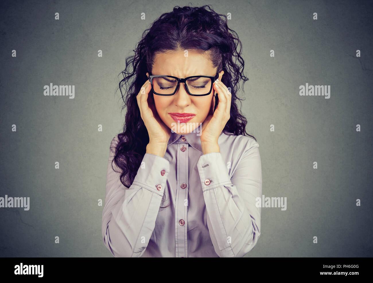 Mujer con gafas sosteniendo los dedos en las sienes intentando concentrarme en la toma de decisiones buscando destacó Imagen De Stock