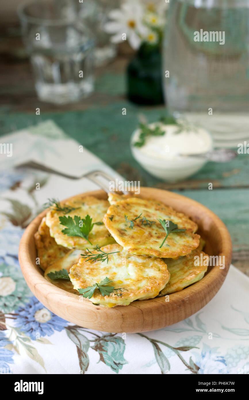 Tortitas con calabacín y maíz dulce, servido con crema agria, perejil y eneldo. Comida vegetariana. Imagen De Stock