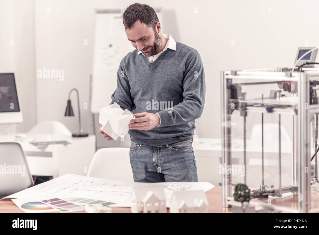 Diseñador ingenioso sosteniendo el modelo de una casa Imagen De Stock