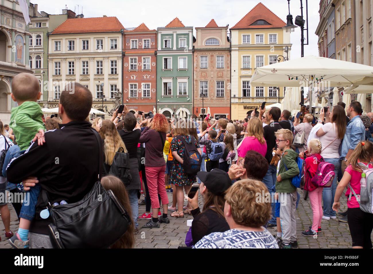 Los turistas están viendo un Poznan cabras - el atractivo turístico de Poznan, disponible todos los días a mediodía en la torre del ayuntamiento de Poznan. Imagen De Stock
