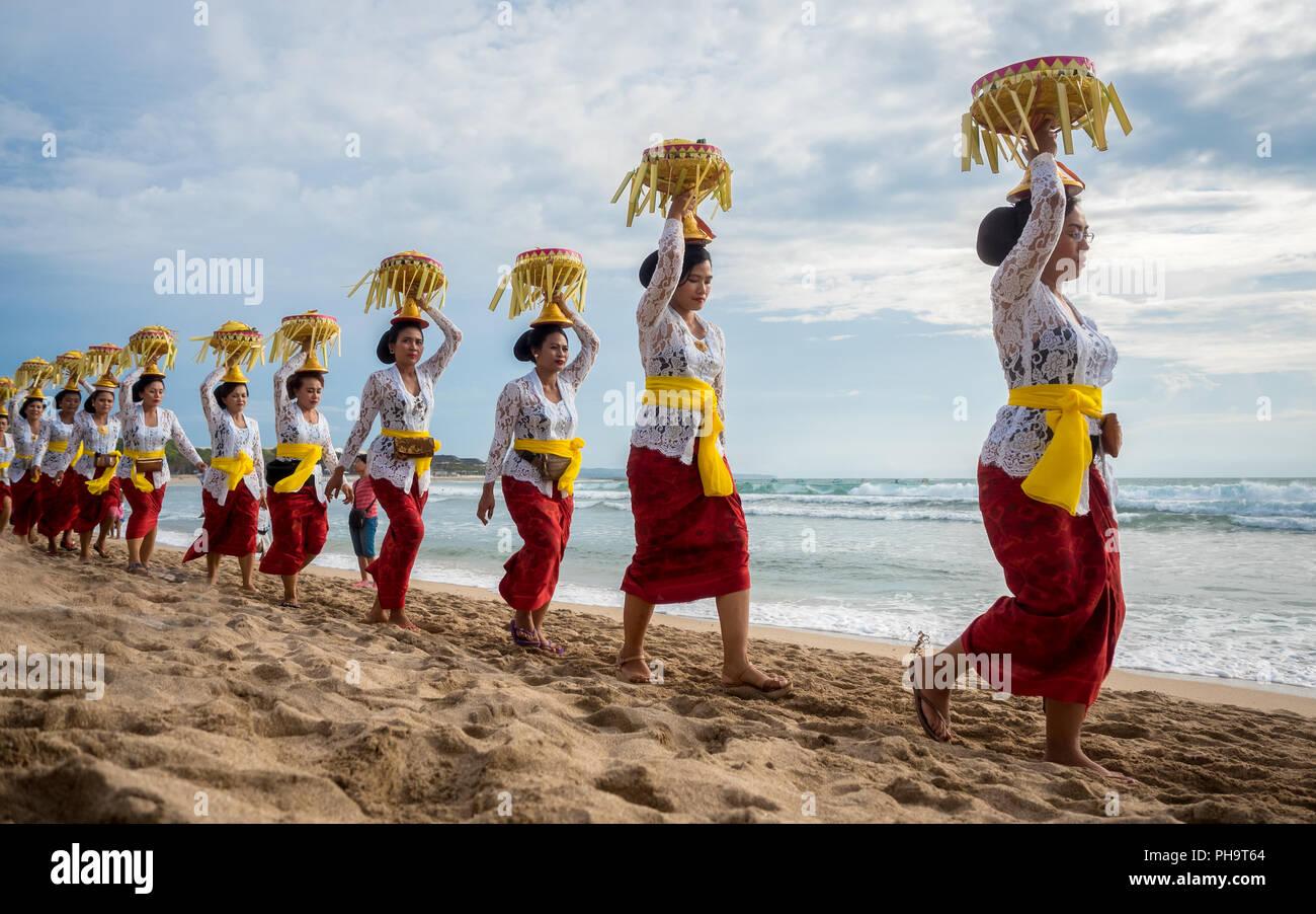 Una línea de mujeres portadoras de ofrendas balinesas sobre sus cabezas en Melasti, la mayor ceremonia de purificación de la Tierra, celebrada en Bali 3 días antes de Nyepi. Imagen De Stock