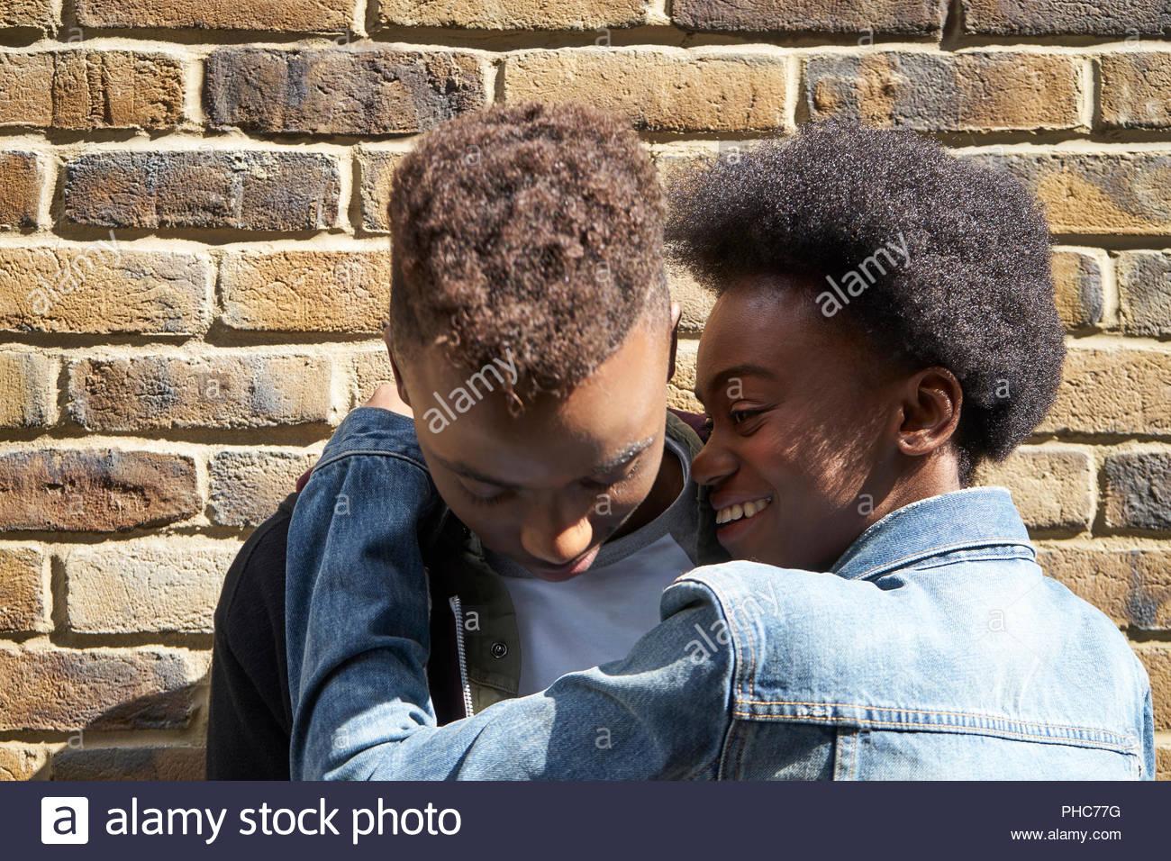 La pareja de adolescentes junto al muro de ladrillo Imagen De Stock