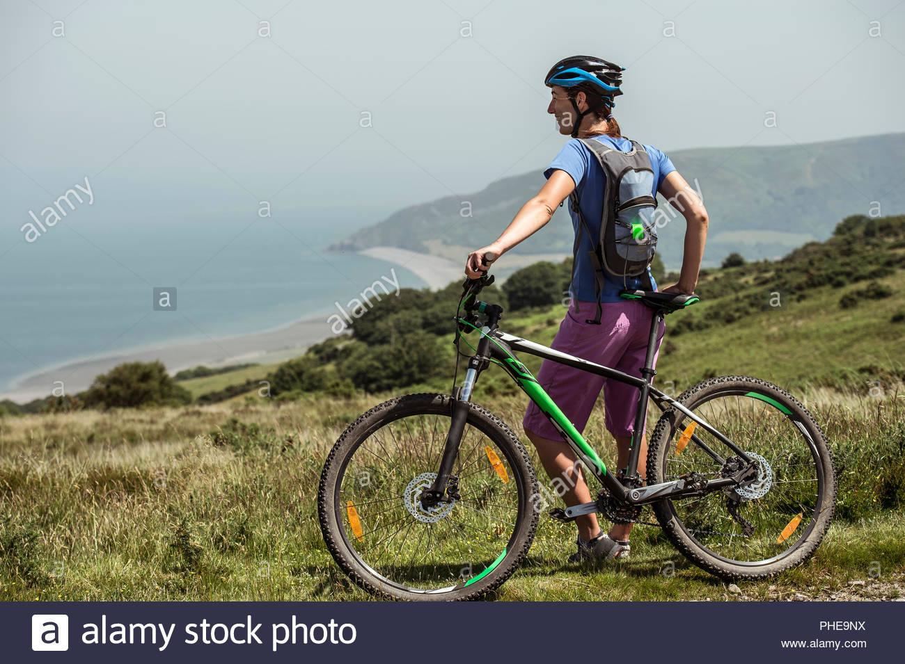 Mujer con bicicleta de montaña en la colina Imagen De Stock