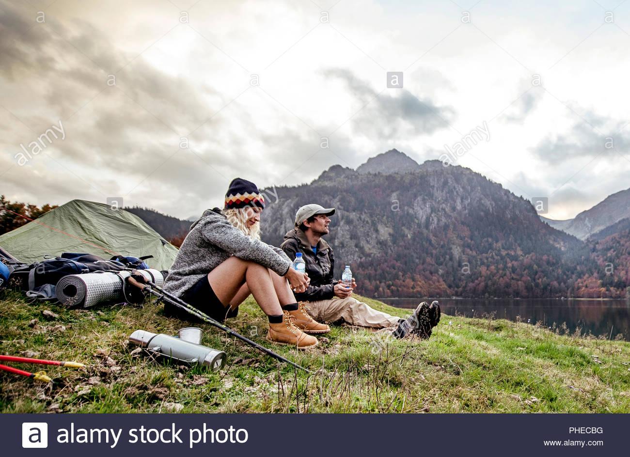 Pareja joven descansando en el campamento al lado de las montañas Imagen De Stock