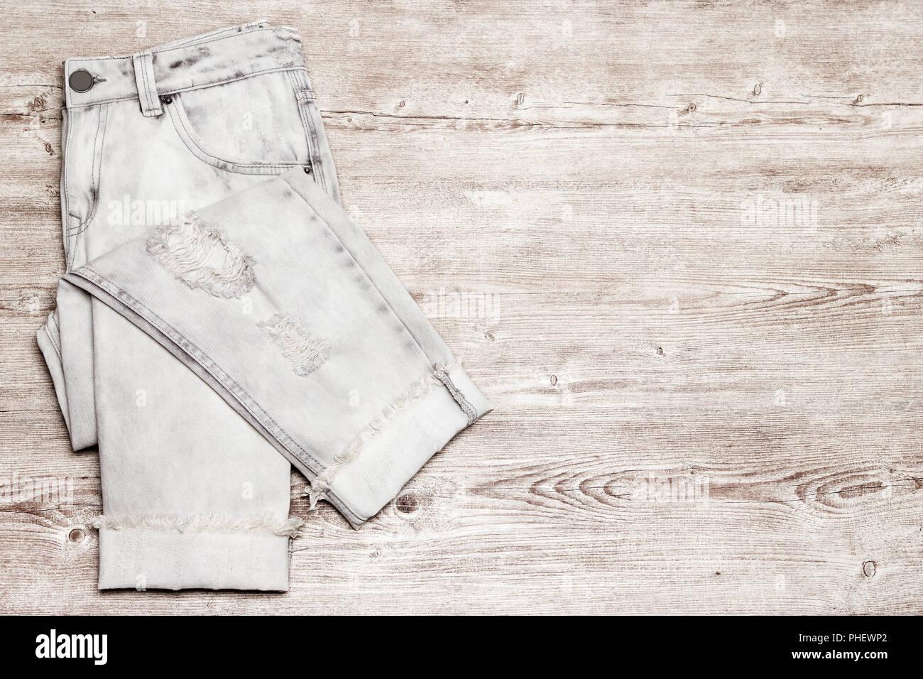 56602ee6d2 Rip pantalones vaqueros rasgados sobre superficie de madera desvencijado