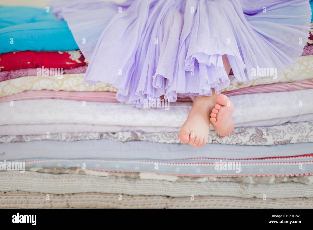 El cuento de hadas de la princesa en un guisante. Niña en color lila tatu falda sentada en la cama alta. Pie desnudo si la niña. Las piernas de una niña sentada en Imagen De Stock
