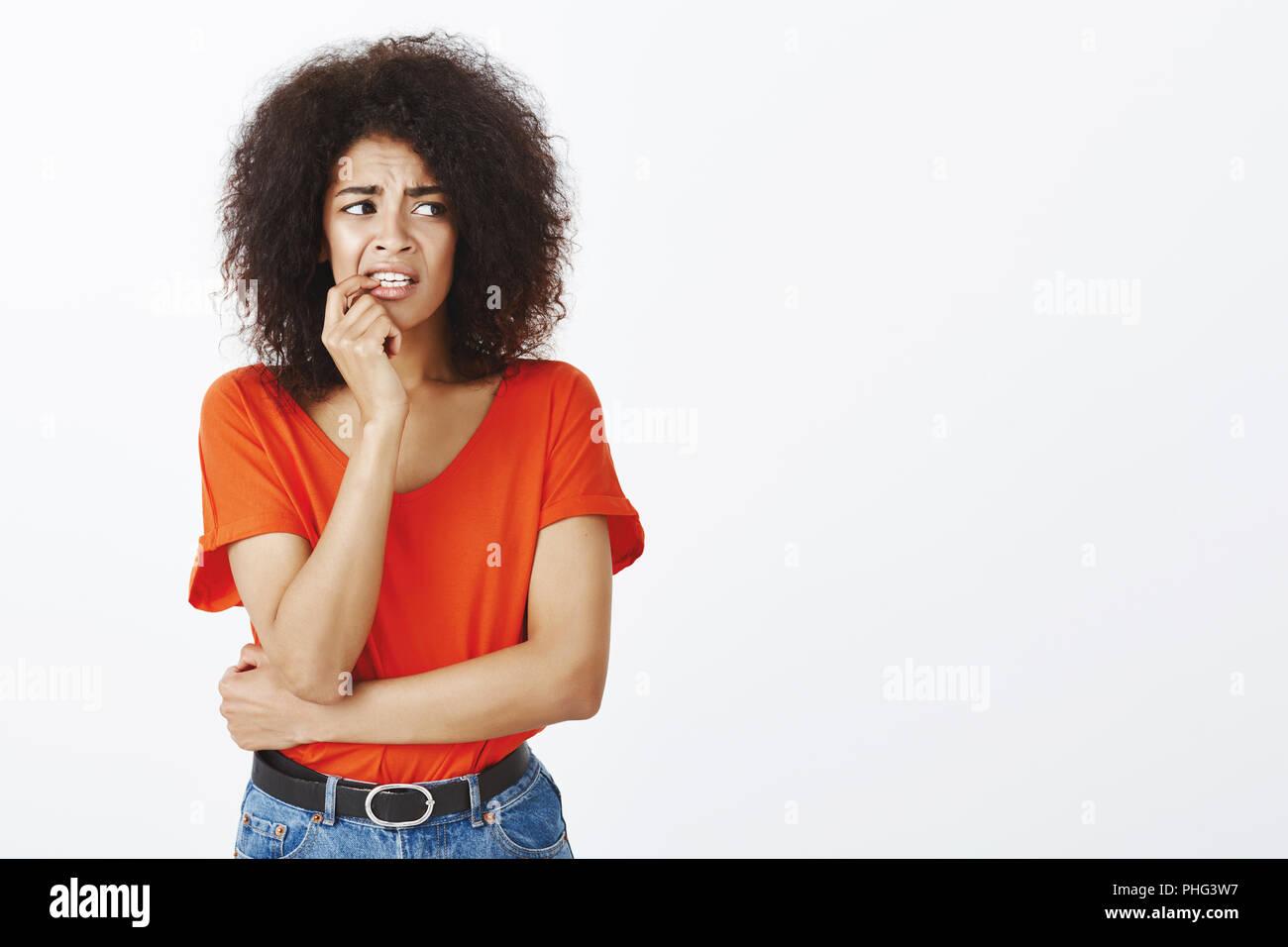 6fd72f577 Chica mordiendo las uñas de nerviosismo. Retrato de ansiosos inseguro  atractivo femenino con peinado afro