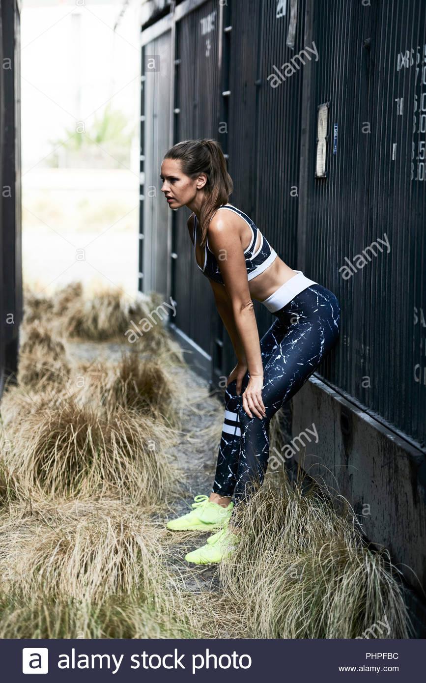 Mujer vistiendo ropa deportiva por contenedor de carga Foto de stock