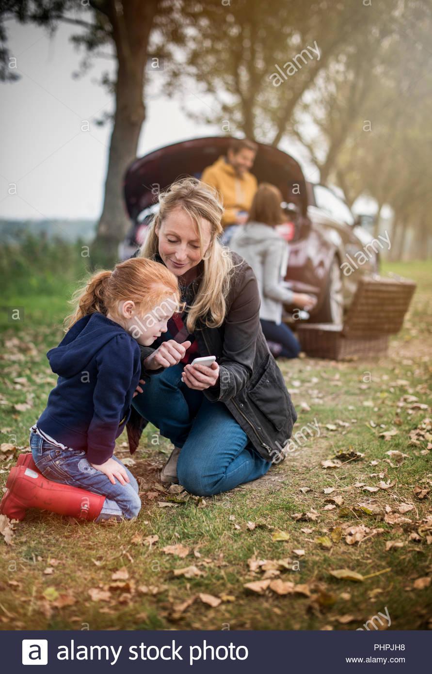 Madre e hija utilizando el teléfono inteligente en el campo Imagen De Stock