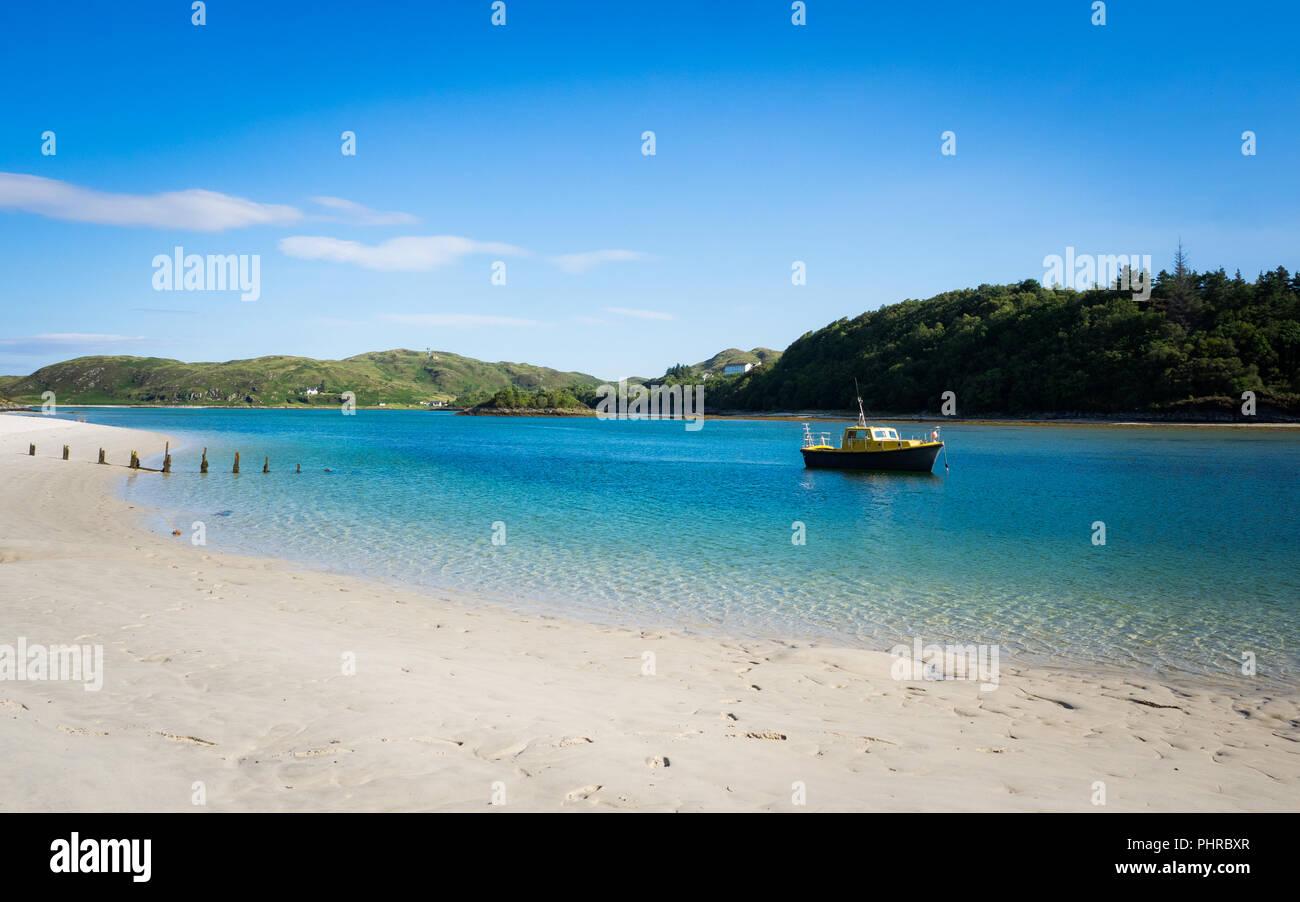 Barco en el agua azul, cerca de una playa con el cielo azul Imagen De Stock