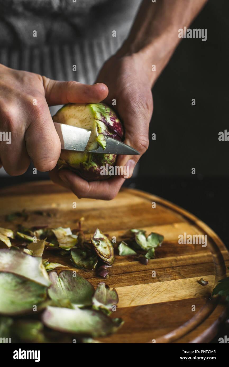 Un hombre prepara una alcachofa Foto de stock