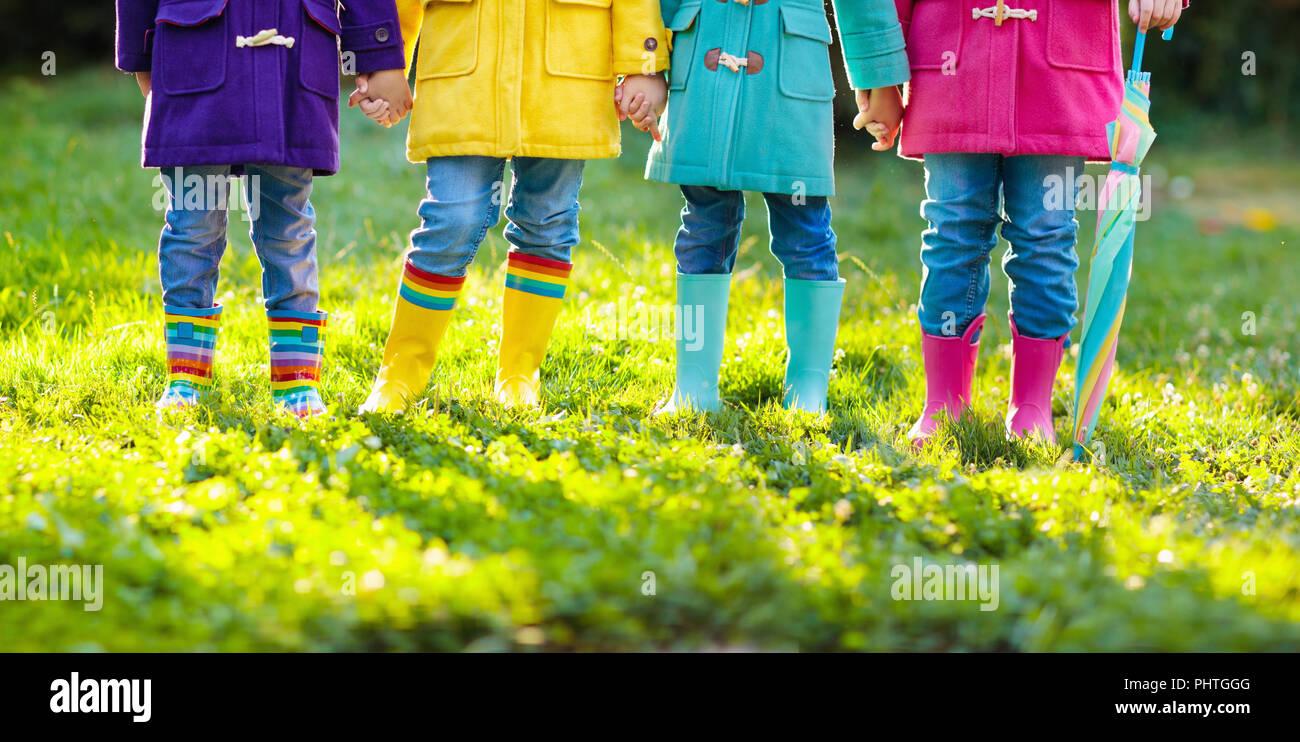 Grupo de niños en botas de agua. Colorido calzado para niños. Los niños y niñas en rainbow wellies y duffle coat. Rainbow calzado y ropa para autu Imagen De Stock