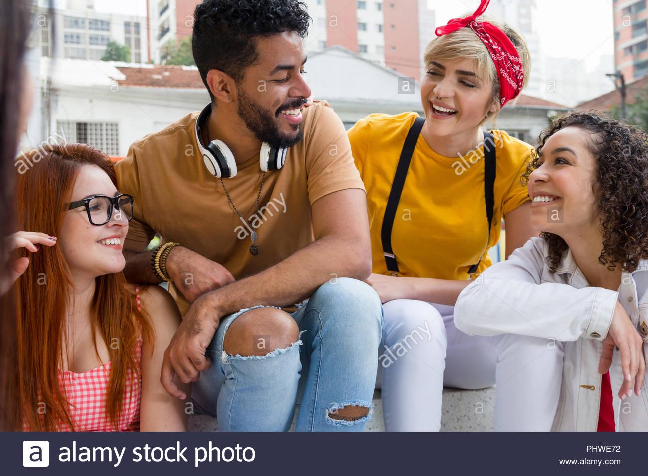 Amigos feliz y sonriente sentado en la cafetería al aire libre. Grupo de raza mixta socializar en un partido en el restaurante exterior. Verano caliente, amistad, buzos Imagen De Stock