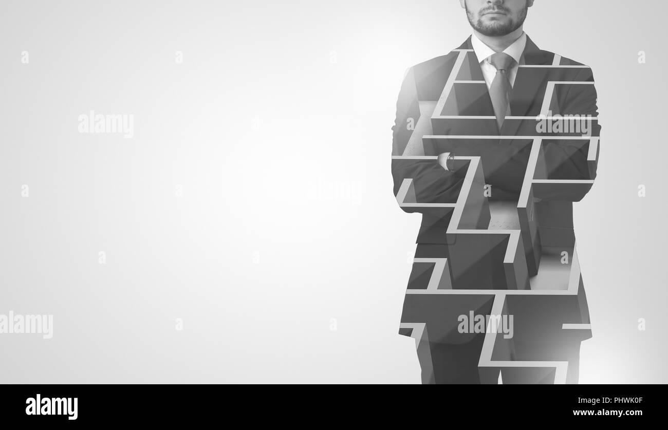 Empresario joven en traje de pie con laberinto gráfico Imagen De Stock