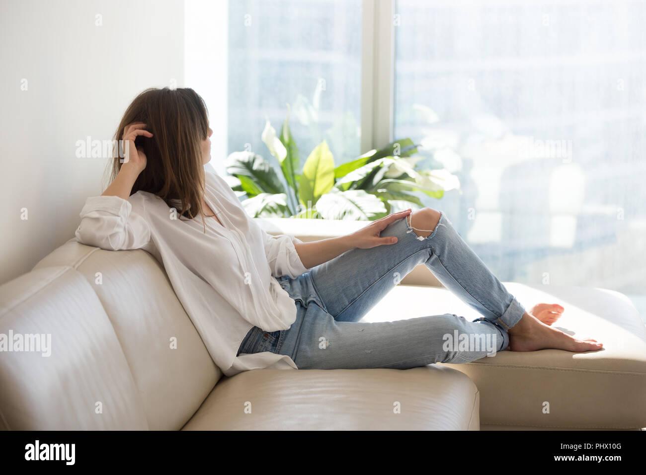 Mujer pensativa relajada disfrutando de bienestar soñando en lujo l Imagen De Stock