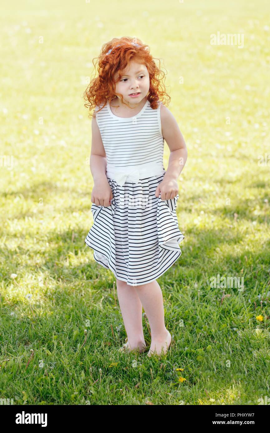 1455e35cc4 Retrato de cute adorable poco asustada pelirroja niña caucásica en vestido  blanco rayado