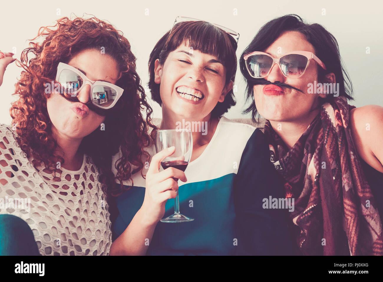 Tres mujeres caucásicas amigos permanecer juntos en la amistad y la locura con pelo como bigote y felicidad relación concepto. vintage pleno c Foto de stock