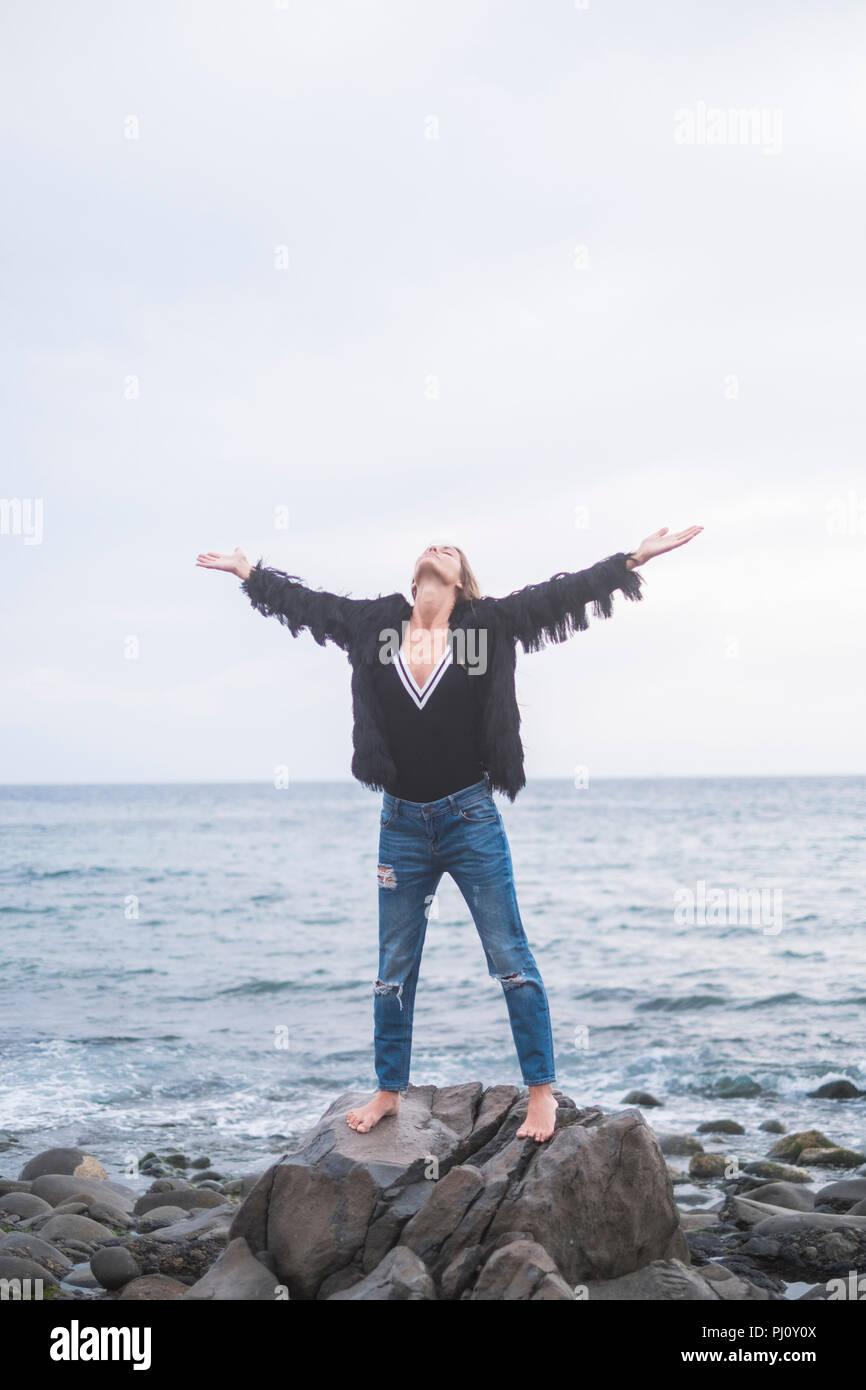 Indie joven mujer caucásica de pie con los brazos abiertos y disfrutar de la naturaleza y la libertad solamente en las rocas en la playa. Ocean casual en el fondo. Imagen De Stock