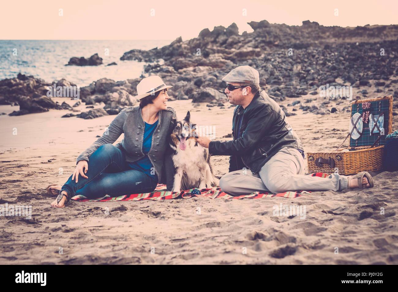 Bonito grupo de perro, un hombre y una mujer jóvenes divirtiéndonos juntos en la playa, hacer un picnic y disfrutar de la actividad de ocio al aire libre, la gente de moda. Imagen De Stock