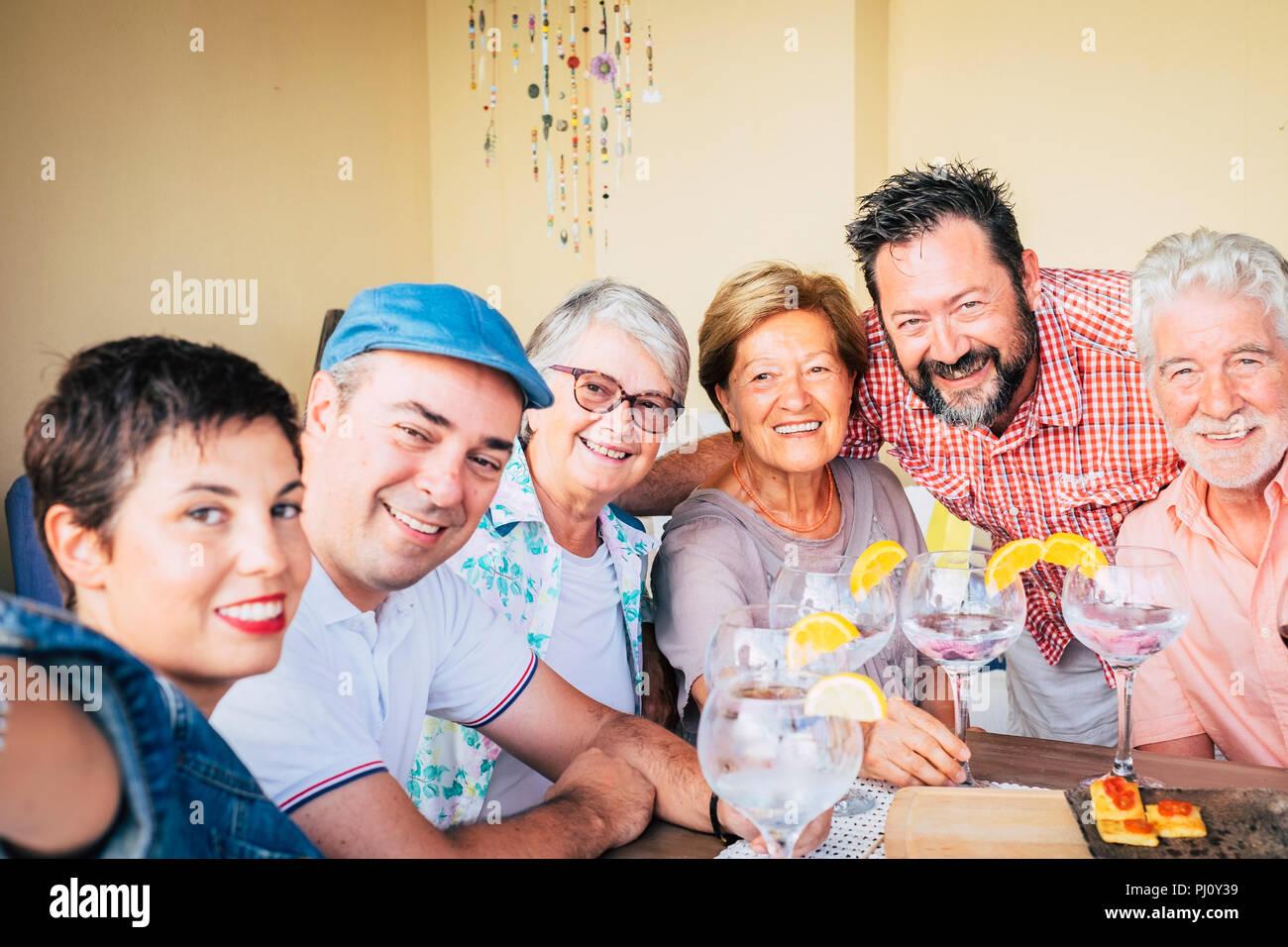 Selfie retrato tomado con teléfono. grupo de edades mixex alegres personas disfrutamos todos juntos celebrando en la mesa, con cócteles y comida. sonrisa peo Imagen De Stock