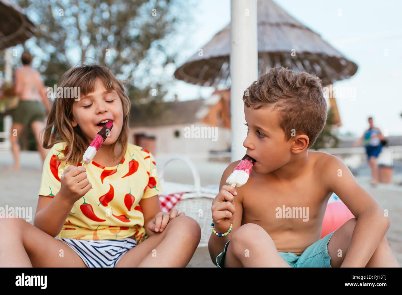 Felices los Niños positivos sentado en la arena de la playa y a comer helado. La gente, los niños, los amigos y la amistad concepto Imagen De Stock