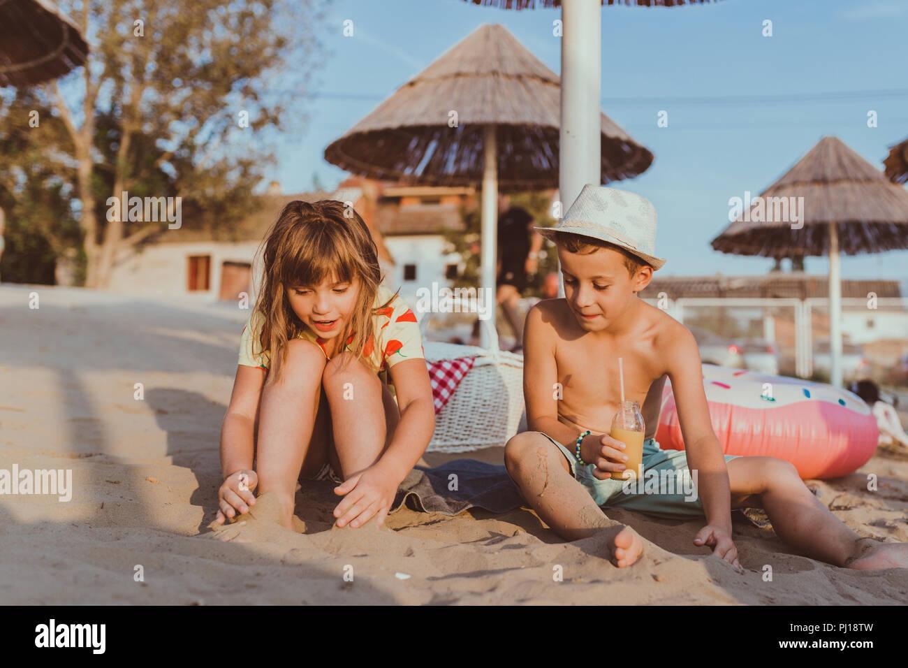 Felices los Niños positivos sentada sobre una toalla en la playa y hablando. Imagen De Stock