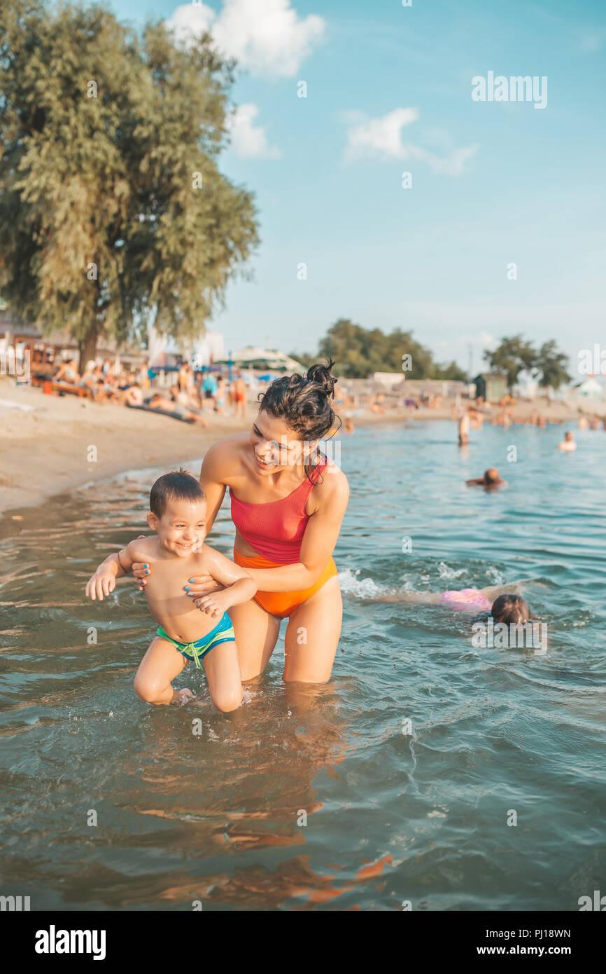 Niño de tres años niño jugando con la madre en el agua. La madre enseña a su hijo a aprender a nadar. Familia Feliz. Vacaciones, viajes concepto Imagen De Stock