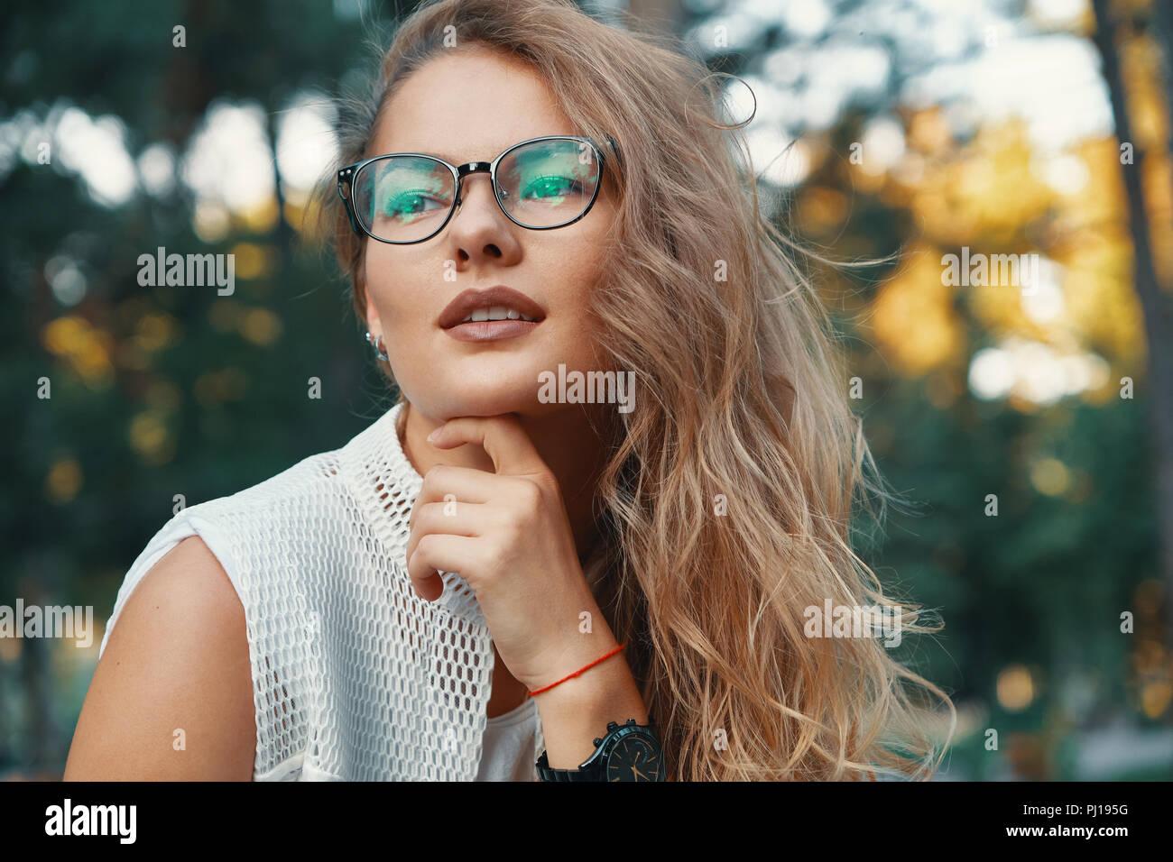 9a4a2657f6 Precioso modelo de gafas. Mujer atractiva con gafas, tocar la barbilla con  una mano mientras sonriendo, mirando a la cámara, vestidas de blanco ropa  de moda ...
