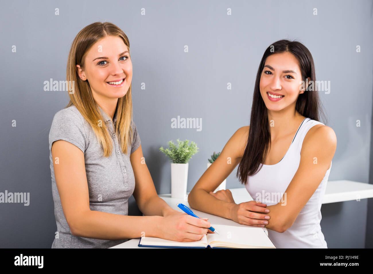 Mujer recepcionista del gimnasio deportivo y una mujer con la conversación acerca de la composición y el ejercicio. Imagen De Stock