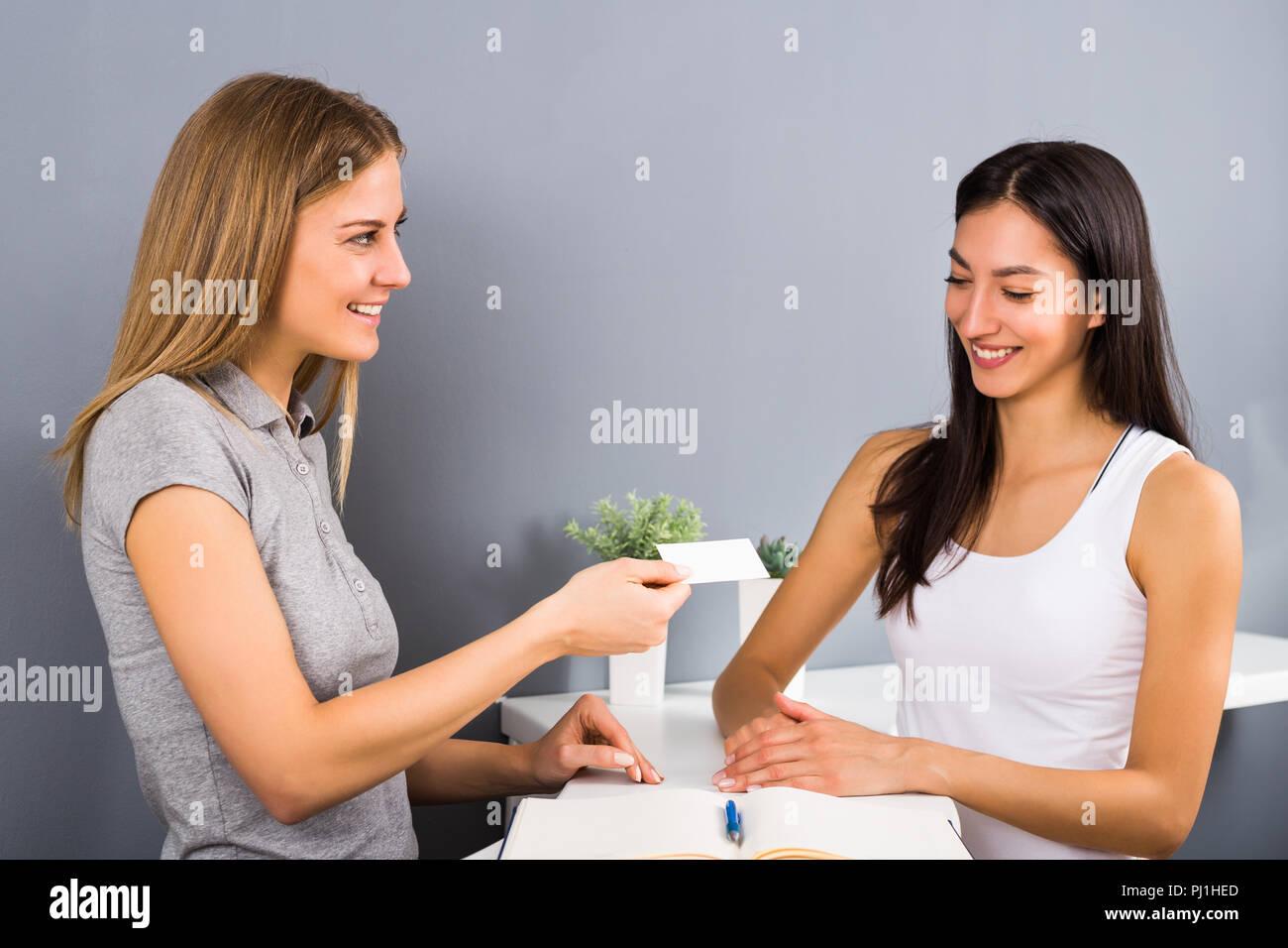 Mujer recepcionista del gimnasio está dando una tarjeta de membresía a la mujer deportiva que vinieron a hacer ejercicio. Imagen De Stock