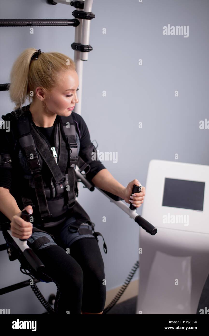 Mujer rubia va a hacer ejercicios con máquina de EMS Imagen De Stock