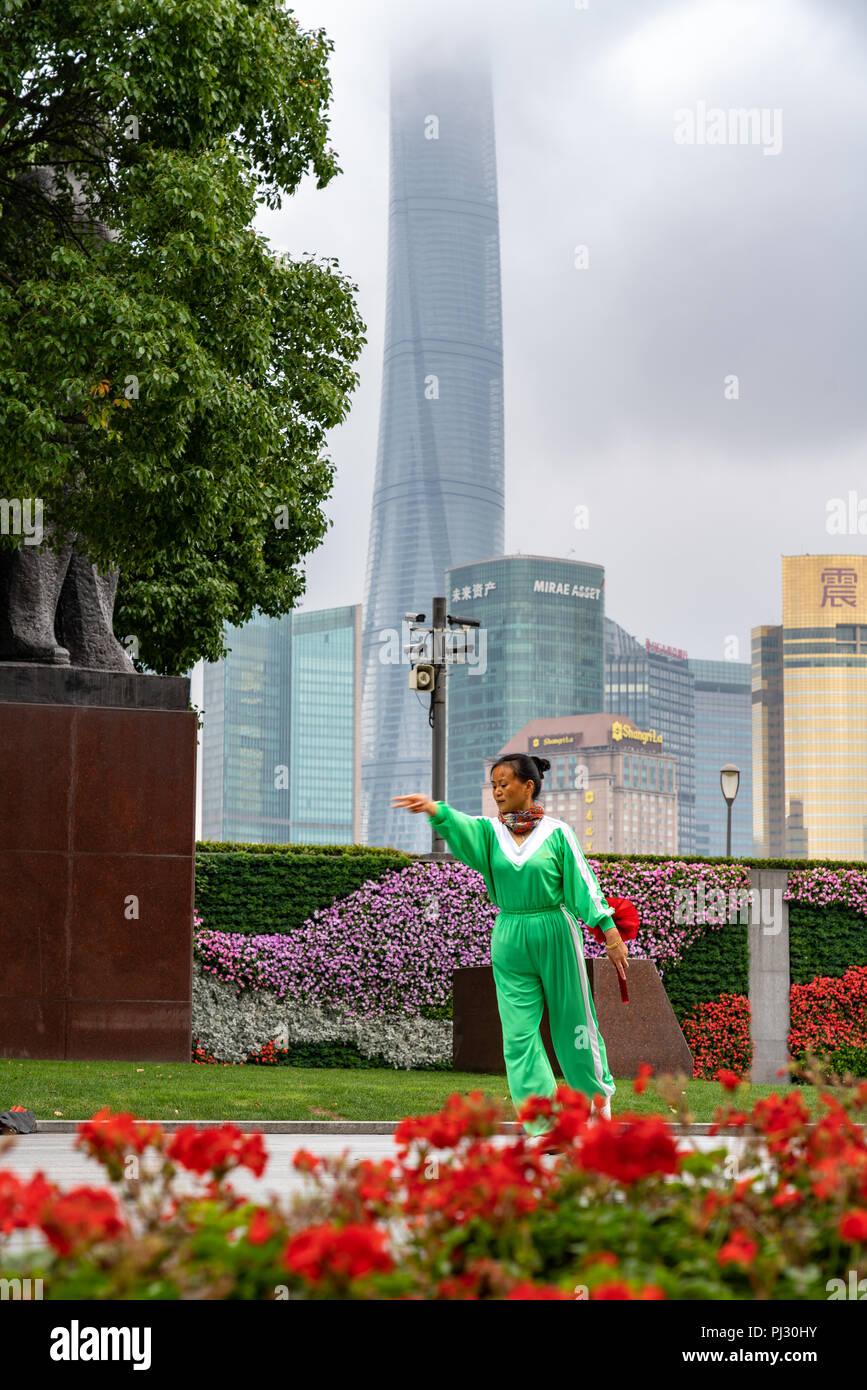 Shanghai, China - La mujer realiza la rutina de ejercicio temprano en la mañana a lo largo del Bund, con el horizonte de Pudong en segundo plano. Imagen De Stock