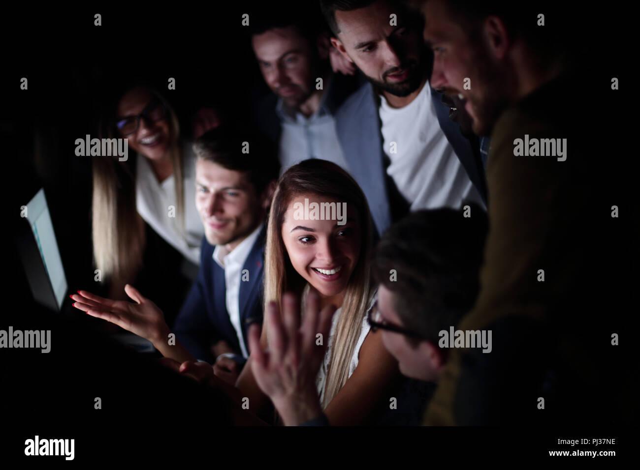 Close up.sonriente equipo empresarial sentado al escritorio tarde. Imagen De Stock