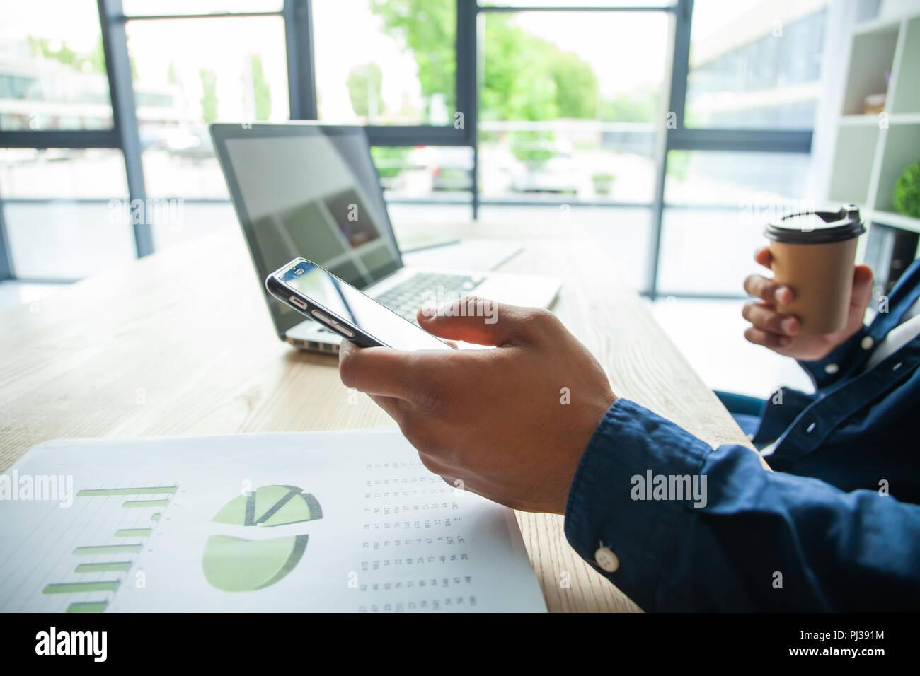 Feliz empresario afroamericano utilizando un teléfono móvil en una oficina. Foto de stock