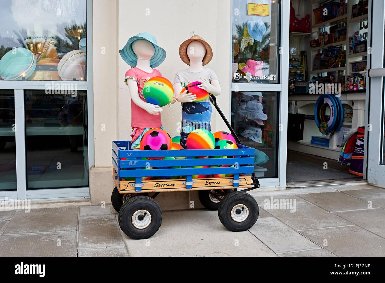 Tienda pantalla exterior de coloridas prendas para niños y juguetes de playa en la parte delantera acera en Seaside, Florida, EE.UU. Imagen De Stock