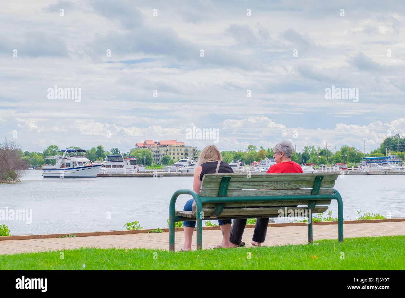 Dos mujeres sentadas en un banco cerca del paseo marítimo a lo largo de la orilla del lago Couchiching en Orillia Ontario Canada. Foto de stock