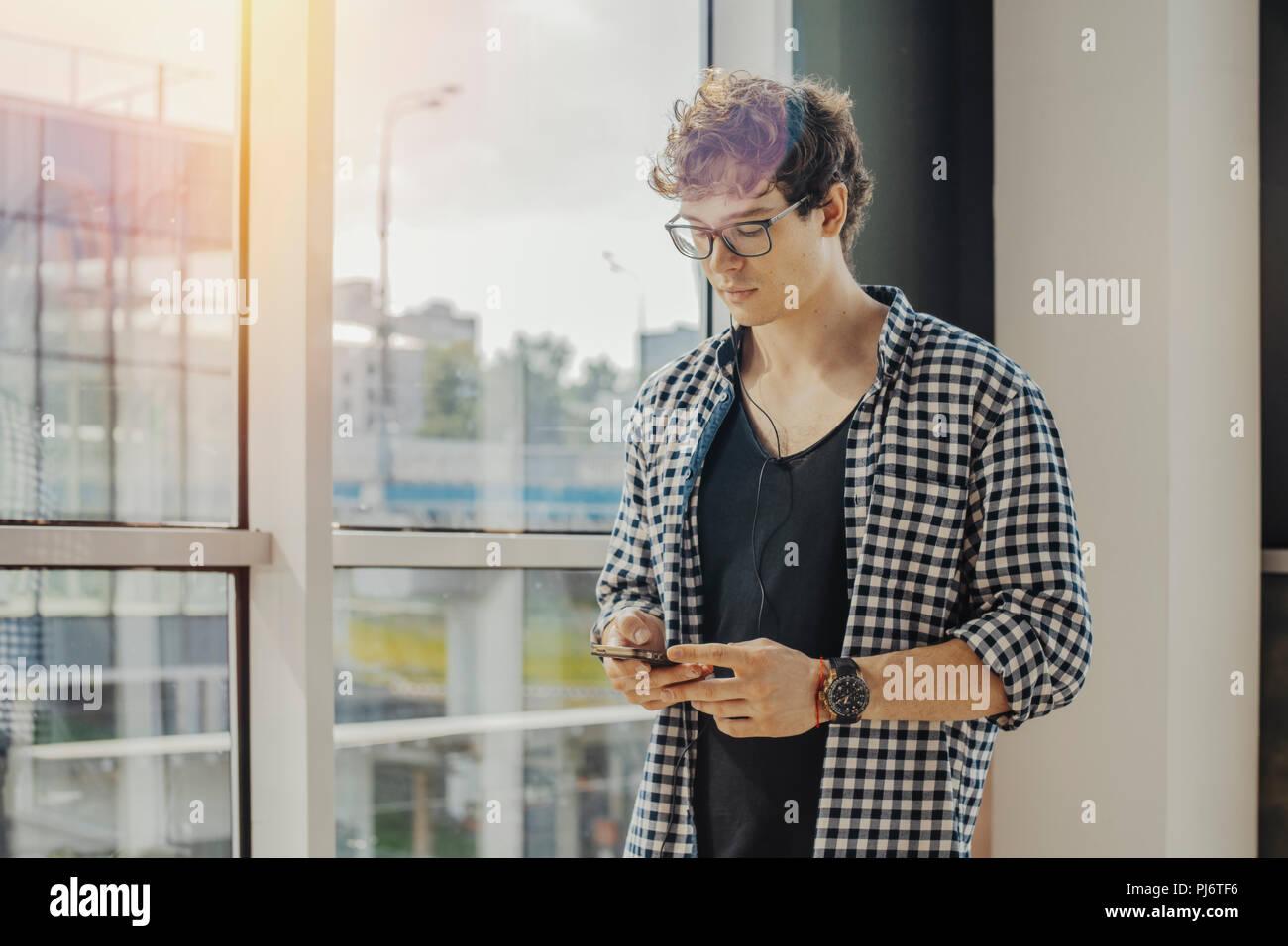 Primer plano de un joven hombre mirando la pantalla del teléfono móvil en la estación de metro. Imagen De Stock