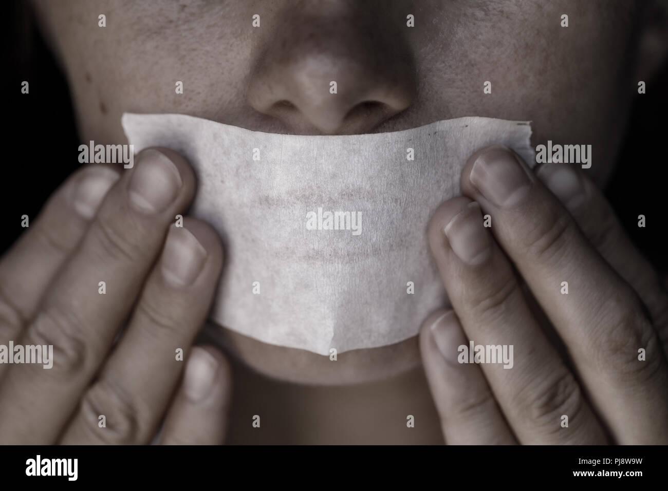Concepto sobre el tema de la libertad de expresión: la cara de la chica está sellada con cinta adhesiva Scotch Tape Imagen De Stock