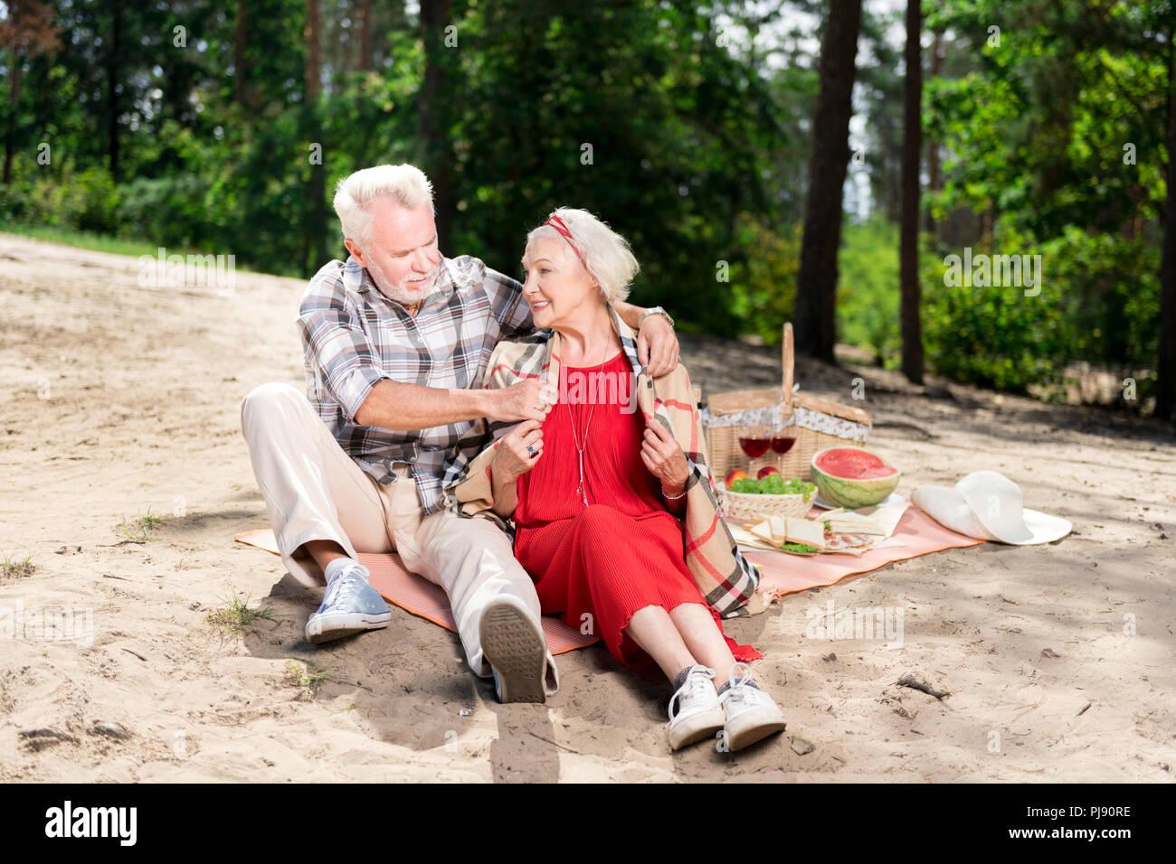 Cuidado anciano marido poniendo tartan plaid sobre su esposa hombros Imagen De Stock