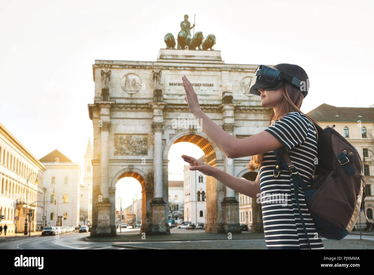 Chica turista en gafas de realidad virtual. Viaje virtual a Alemania. El concepto de turismo virtual. Excursión arco triunfal en Munich en el fondo. Imagen De Stock