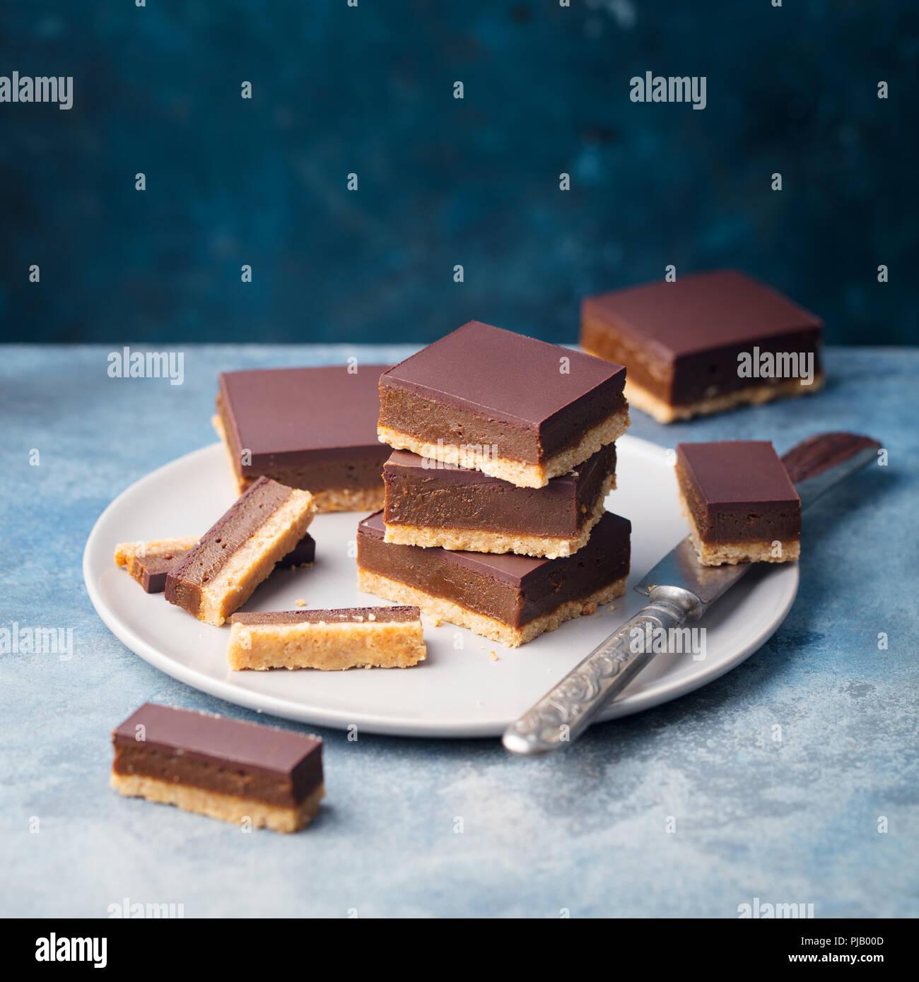 Cortes, barras de caramelo de chocolate, millonarios en un plato de galletas de mantequilla. Fondo azul. Copie el espacio. Imagen De Stock