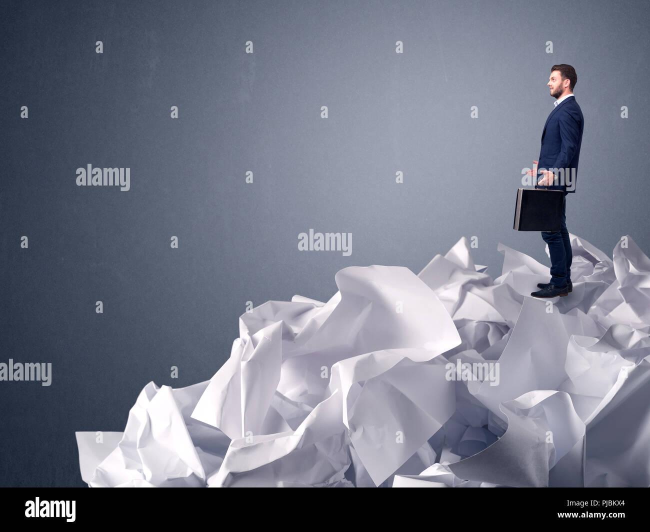 Pensativo joven empresario de pie sobre un montón de papel arrugado con un fondo gris claro Foto de stock