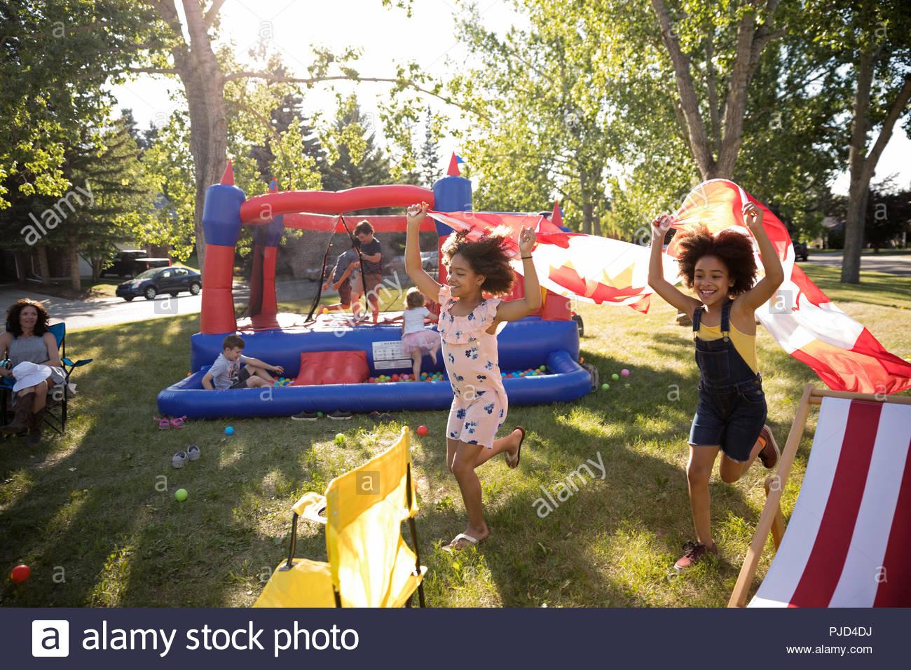 Juguetón niñas corriendo con banderas Canadienses, celebrando el Día de Canadá en sunny park Imagen De Stock