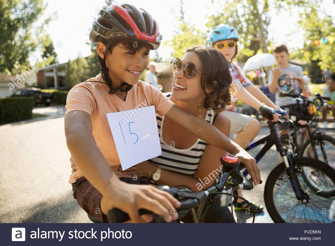 Feliz madre e hijo preparándose para bicicleta de carrera en verano barrio block party Imagen De Stock