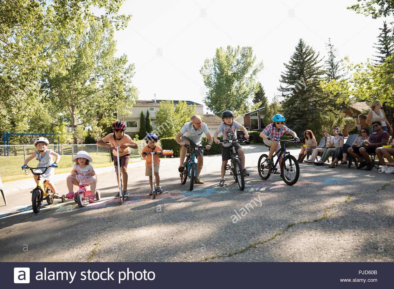 Los niños estén listos para la carrera de bicicletas en la línea de partida en el verano barrio block party Imagen De Stock