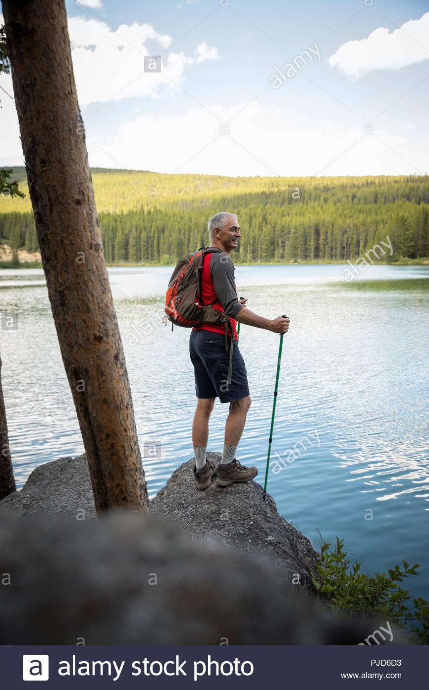 Hombre maduro, senderismo con nordic walking polacos, disfrutando de la tranquila vista de Forest Lake, Alberta, Canada Foto de stock