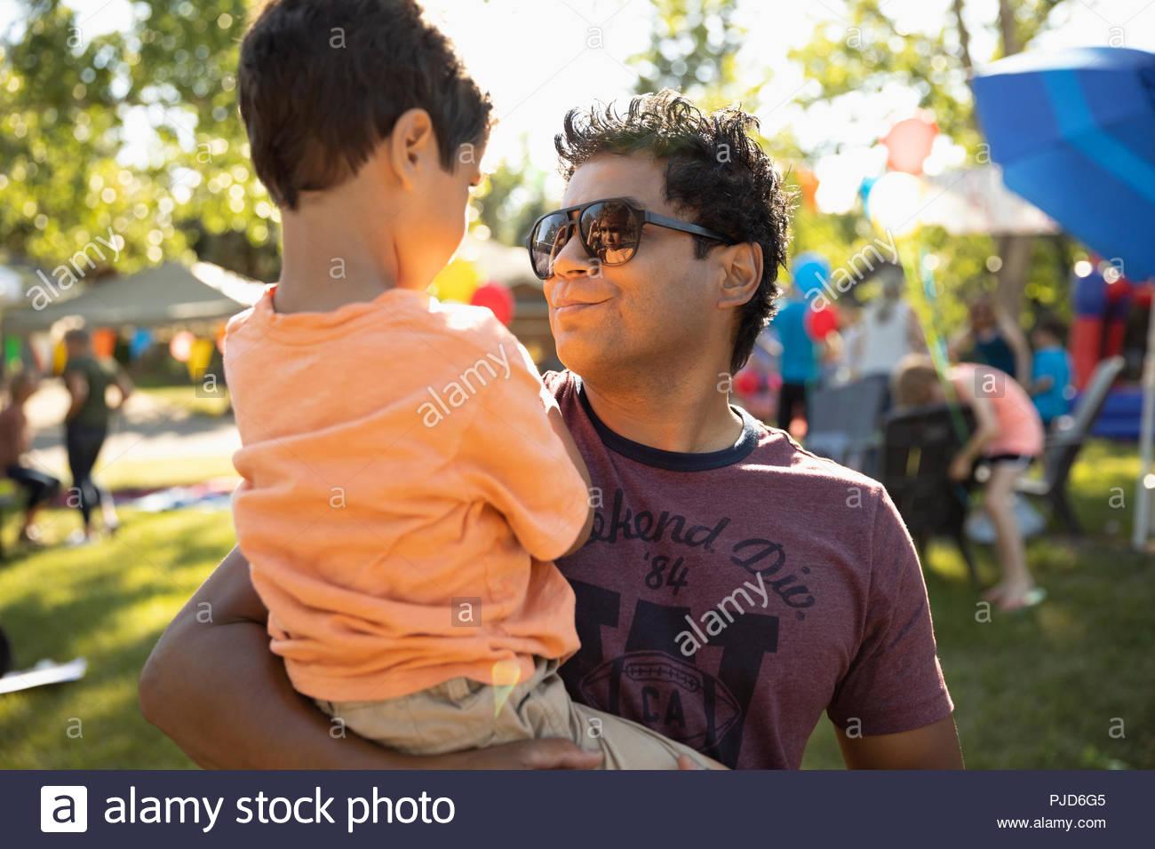 Hijo de padre sosteniendo en el verano barrio block party Imagen De Stock