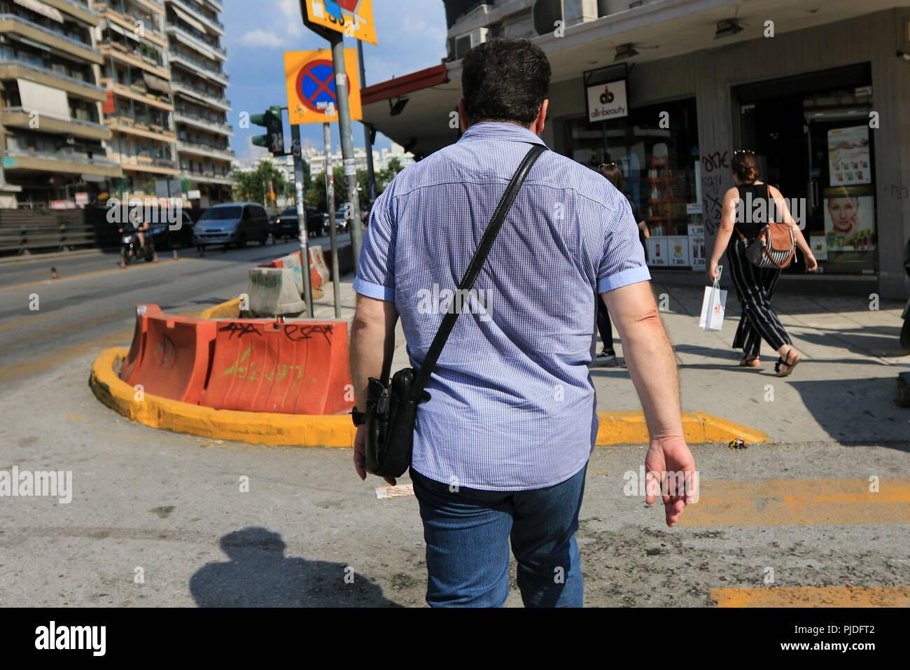 Hombre caminando por la calle con la espalda de su camisa empapado en sudor Imagen De Stock